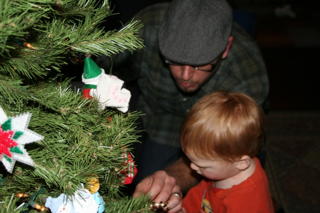 "Luke showing ""Big Red"" how to attach an ornament."